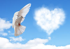 Blue sky with hearts shape clouds and dove. Stock Photo
