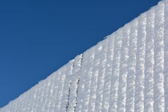 Blue sky and hoarfrost on iron fence Stock Images