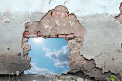 Blue sky hole in aged brick wall Stock Photo