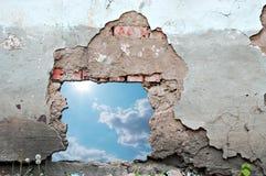 Blue sky hole in aged brick wall stock photo