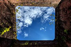 Blue sky in hole in old wall. Brick frame.selective focus Royalty Free Stock Images