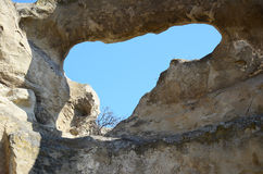 Blue sky through hole in the wall in Old cave city Uplistsikhe, Georgia. Uplistsikhe, GE-March,4 2015: Old cave city Uplistsikhe in Caucasus region, Georgia Royalty Free Stock Photography