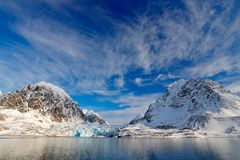 Blue sky with ice floe. Beautiful landscape. Cold sea water. Land of ice. Travelling in Arctic Norway. White snowy mountain, blue stock photo