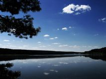 The blue sky in the lake. A little lake and the the blue cloudy sky over it stock photo