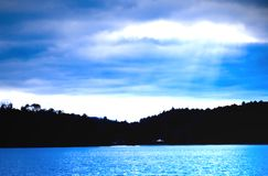 Blue Sky and Lake/Silhouette. A blue tinted landscape with hills and lake. The clouds are parted with rays shining through. A soft blur was added for effect royalty free stock photography