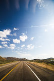Blue Sky Over Empty Highway. Blue sky with light clouds over empty desert highway Royalty Free Stock Photos