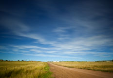 Sky over road and fields. Blue sky with light clouds over a landscape with fields and a road Royalty Free Stock Photo
