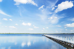Blue sky with light clouds, water, white pier in the summer day. Stock Images