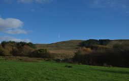 Blue sky looking over field, green grass on hill side, minimal clouds, photo taken in the UK stock photos