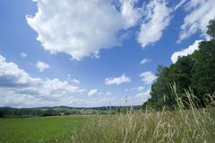 Blue sky and lovely clouds over the summer meadow. Peaceful and sunny landscape royalty free stock image