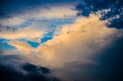 Blue sky with many layers of clouds. With yellow glow and dark blue spots stock images