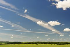 Blue sky with many white clouds and narrow green field copyspace Royalty Free Stock Photos