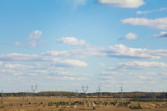 Blue sky on a meadow with high-voltage wires. Blue sky with clouds on a meadow with high-voltage wires and oil pumps Stock Image