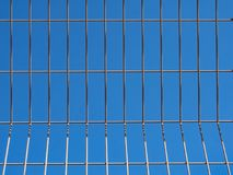 A blue sky through a metal lattice. Fragment of a metal grid on a background of blue color Stock Photo