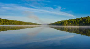 Blue sky misty summer morning in middle of Corry lake. Royalty Free Stock Photos