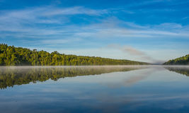 Blue sky misty summer morning in middle of Corry lake. Stock Image