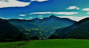Blue sky, mountains and green meadows Stock Photography
