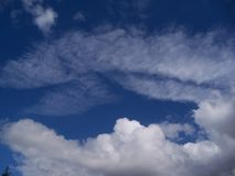 Blue sky and multiple kinds of white clouds. Bright blue sky with different kinds of white clouds showing portents of the weather to come royalty free stock photo