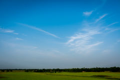 Blue sky with open grass field Stock Images