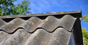 Blue sky over the dangerous asbestos old roof tiles. Able to use as background Royalty Free Stock Images