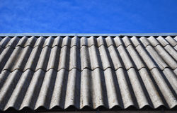 Blue sky over the dangerous asbestos old roof tiles Royalty Free Stock Photos