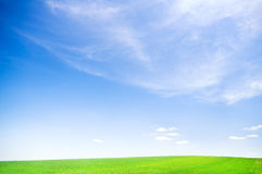 Blue sky over green field Stock Photos