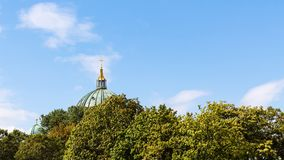 Blue sky over green foliage and dome of Cathedral royalty free stock photography