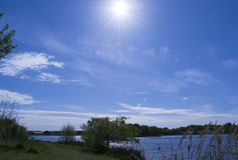 Blue Sky Over Lake With Dramatic Clouds And Sun Beams Royalty Free Stock Photography
