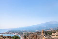 Blue sky over Mount Etna and Ionian sea coast. Travel to Sicily, Italy - blue sky over Mount Etna, Giardini Naxos town on Ionian sea coast and Taormina city in Royalty Free Stock Images