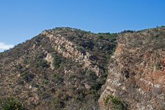DIAGONAL STREAKS OF ROCK RUNNING THROUGH THE SIDE OF A HILL. Blue sky over a mountain range exposing white quartzite layer and red shale stock photography