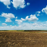 Blue sky over plowed field. Blue cloudy sky over plowed field Royalty Free Stock Photography