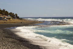 A blue sky over the rocky beach and bay at Playa Las Americas with the surf breaking on the shoreline Stock Photography