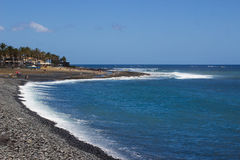 A blue sky over the rocky beach and bay at Playa Las Americas with the surf breaking on the shoreline. A blue sky over the rocky beach and bay at Playa Las Royalty Free Stock Photography