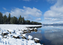Blue sky over snowy winter mountain lake scene Stock Photos