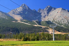 Blue sky over sunny Lomnicky peak, ski slopes and cable cars. The Lomnicky and Kezmarsky peaks High Tatras, Tatra National Park, Slovakia in sunny autumn day Stock Photography