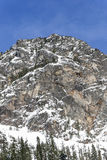 Blue Sky Over Tall Rocky Summit Peak Covered in Winter Snow in Mountain Forest Royalty Free Stock Photography