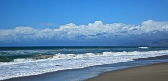 Oxnard California coastline. Blue sky blue Pacific Ocean white splashing waves and white clouds over mountains along California coastline in Oxnard Royalty Free Stock Photography