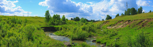 Blue sky panorama with clouds over tops of trees Royalty Free Stock Photography