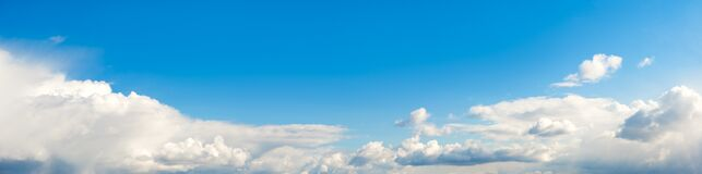Blue sky panorama with white clouds and sun  rays. Summer spring heaven concept. Background for textures backgrounds and web banne