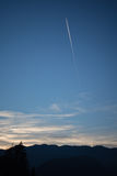Blue sky with plane trail background and silhouette of mountains Royalty Free Stock Image