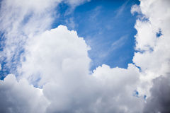 Blue sky with puffly clouds. Image of a bright blue sky framed by big puffy clouds stock image