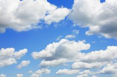Blue Sky and puffy clouds. A horizontal shot of bright blue sky with puffy white clouds