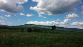 Blue sky, puffy clouds and green terrain Royalty Free Stock Photography
