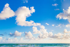 Blue sky, puffy clouds, and ocean Stock Photo
