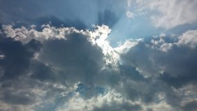 Blue sky, puffy clouds and oh my god a bright light. A horizontal shot of bright blue sky with puffy white cloud formations Stock Photos