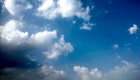 Blue Sky and puffy white & black clouds Royalty Free Stock Photography