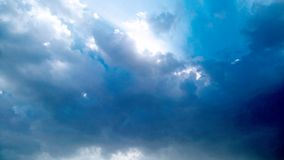Blue Sky and puffy white & black clouds Stock Image
