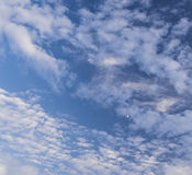 Blue sky with puffy white clouds and a half moon Royalty Free Stock Photo