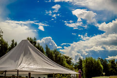 Blue sky after rain. With the sun reflecting on the tent roof Royalty Free Stock Photo