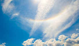 Blue sky rainbow. A beautiful Spring day with blue skis, billowy clouds and an upside-down rainbow Royalty Free Stock Image